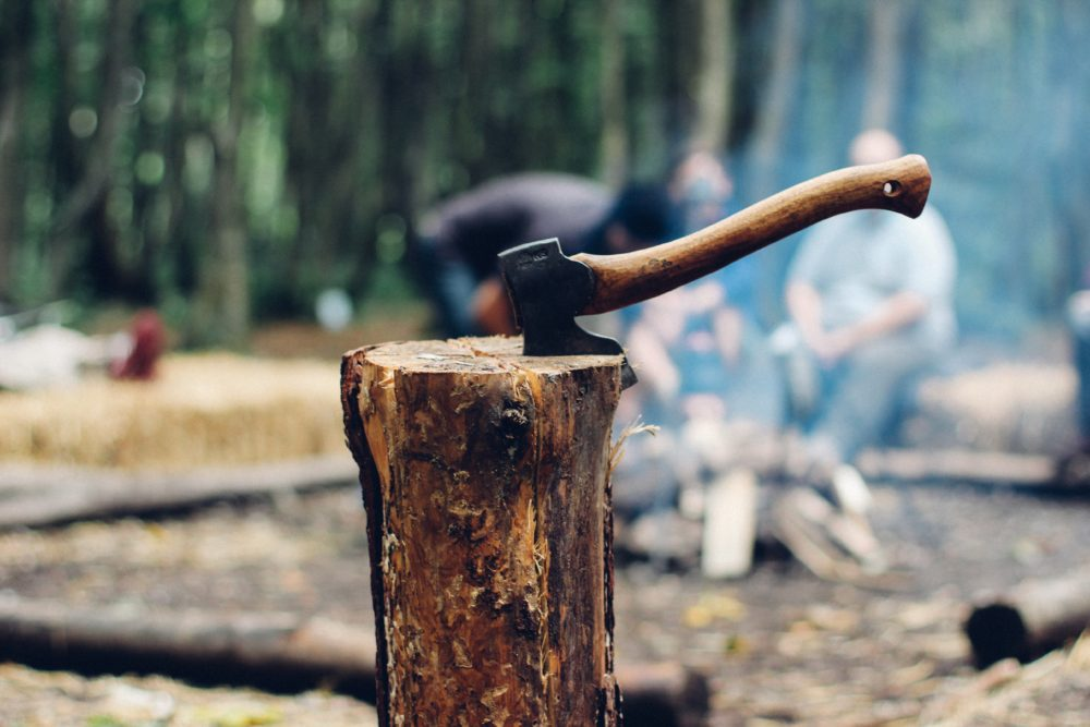 A camping hatchet in a wooden log.