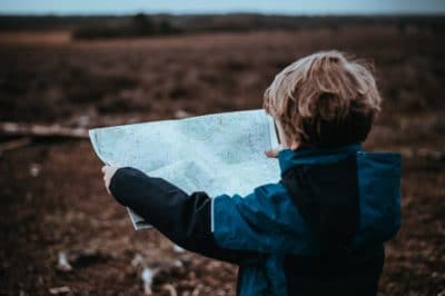 A boy reading a map outside.
