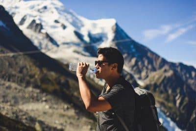 A man drinking a bottle of water in the mountains.
