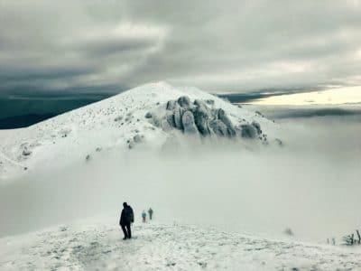 A mountain hiker on a snow mountain top.