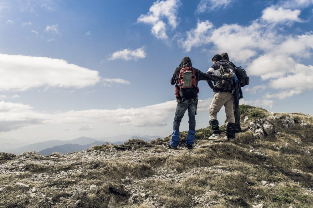 Two men on a mountain wearing gaiters.