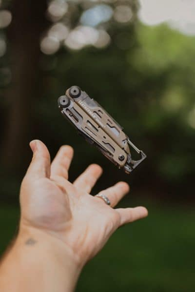A hand throwing a Leatherman knife into the air.