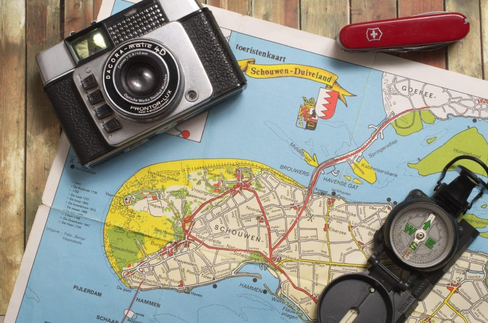 A map with a swiss army knife, compass, and camera.