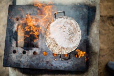 A kettle boiling food over a fire.