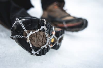 A boot in the snow with a gaiter.