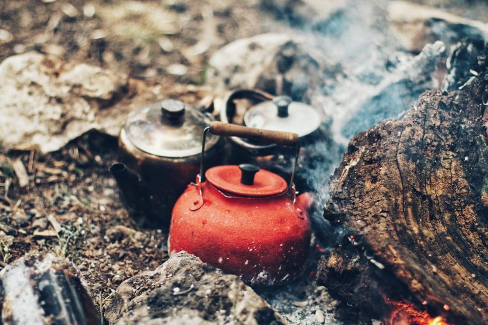 A red kettle pot on a fire.