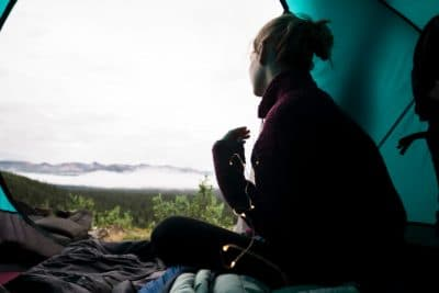 A girl inside a tent, looking out.