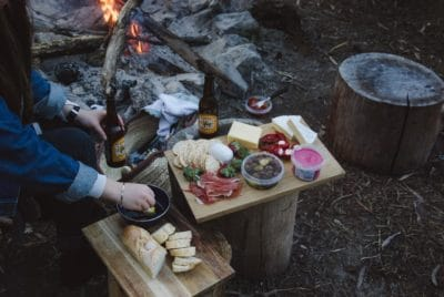 A wooden plate of crackers, meat, and cheese by a fire.