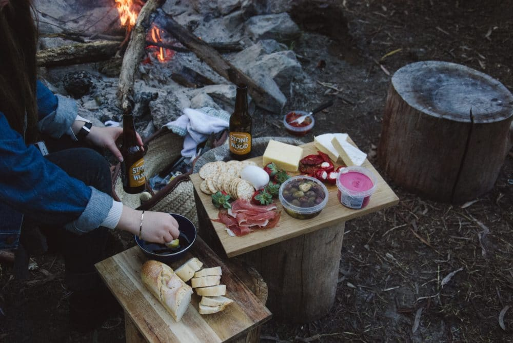 People camping, eating food by the campfire.