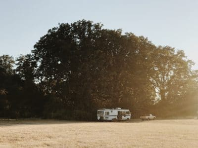A white RV camper in a field.