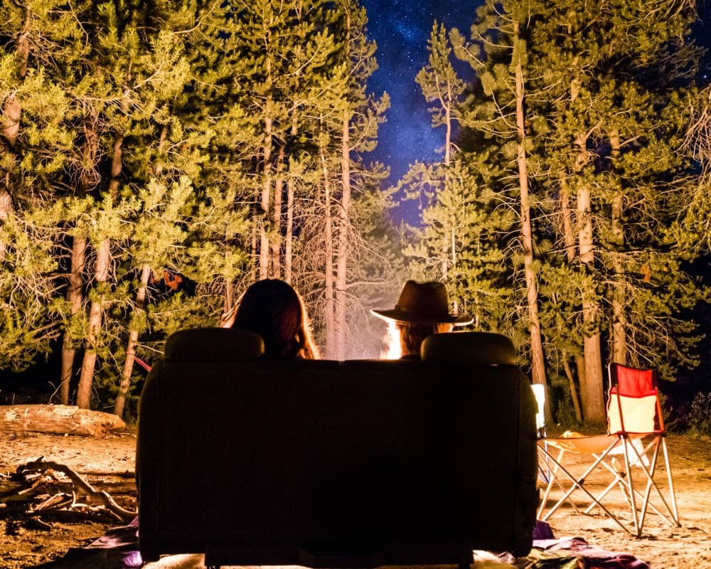Two people sitting on a couch by the fire in the woods.