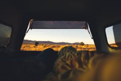 A sleeping back in a camper van with a view of nature.