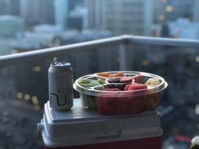 A bowl of fruit and a canned drink on top of a cooler.
