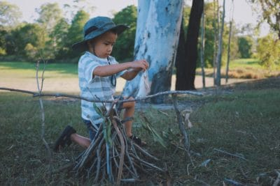 A boy building a stick house.