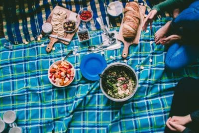 Am assortment of food on a blue blanket.