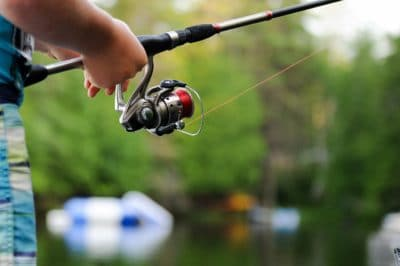 A fishing rod with a reel and line on a lake.