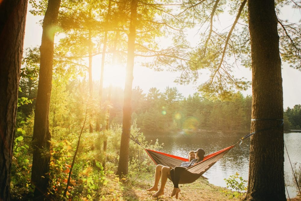 A girl and a guy in a camping hammock in the woods.