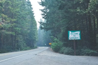 A sign that says welcome to Oregon on the side of a road.