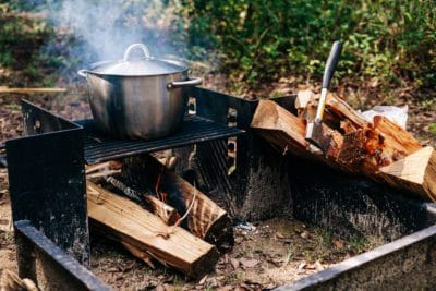 A pot cooking over a fire in the woods.