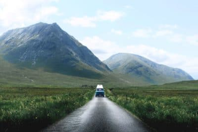 A RV driving down the road with mountains in the background.