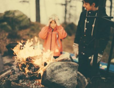 A girl and boy by a campfire.