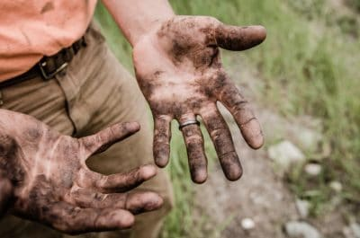 A man looking at his dirty hands.
