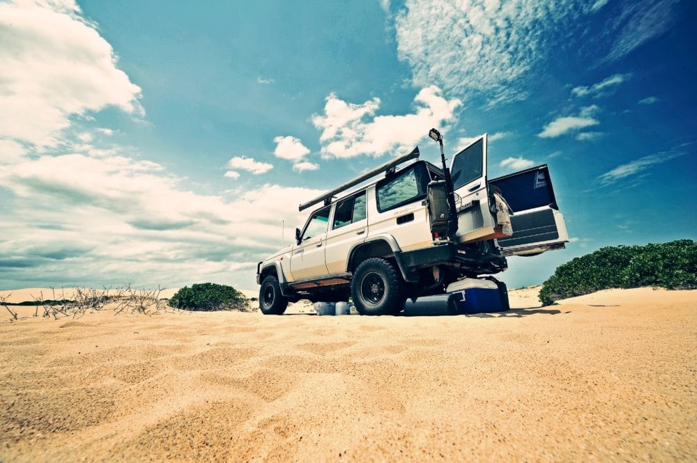 A white Jeep with a cooler behind it in the sand.