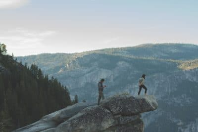 Two men atop a rock on a mountain ledge.
