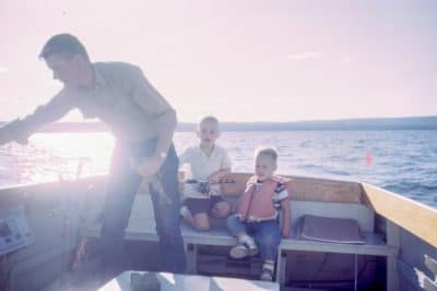 A family on a fishing boat on a lake.