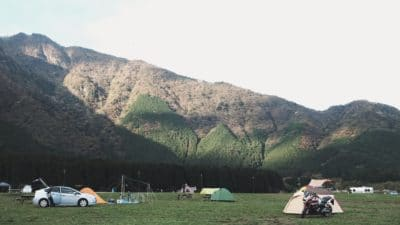 A campsite in a field with cars.