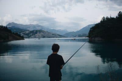 A boy fishing on a lake.