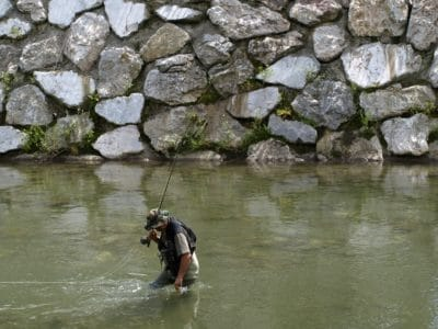 A man fly fishing in a reservoir.