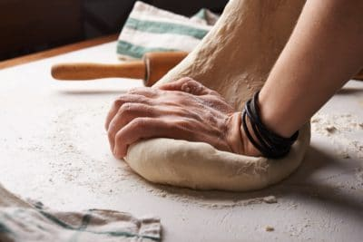 Someone forming a ball of dough.