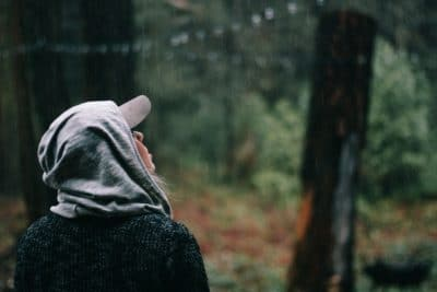 A girl with a hat in the rain in the woods.