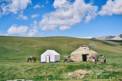 Some campers with horses and tents in a green field.