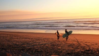 Two people with surfboards on the beach.