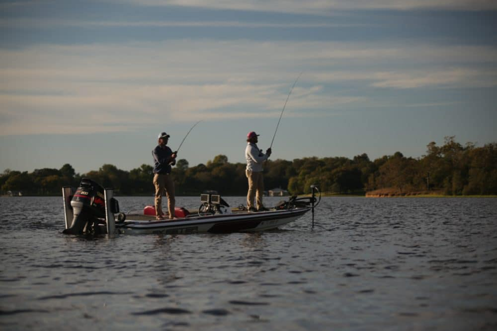 A couple of men fishing from a boat on a lake.