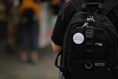 A person wearing a black backpack with a pin that says facts matter.