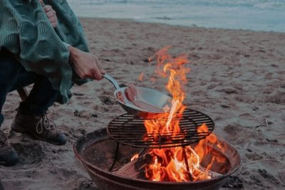 A person cooking bacon over an open fire on the beach.