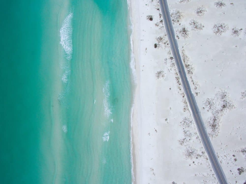 Arial view of the sea and beach with a road.