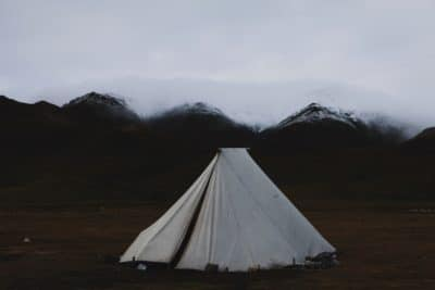 A white canvas tent in the middle of a field.