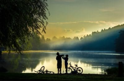 Two boys fishing on a lake.