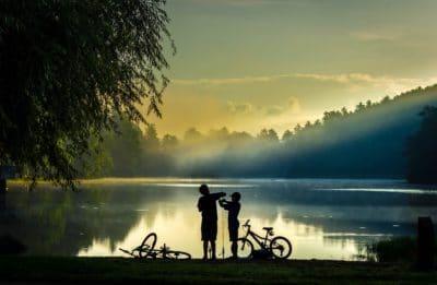 Two boys fishing on a lake.