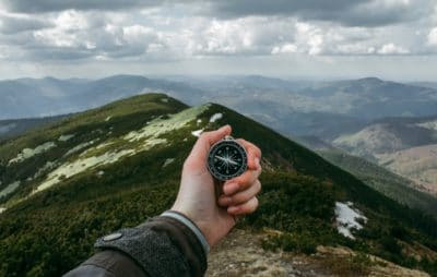 A hand holding a compass on the mountain.