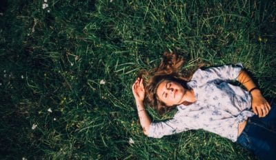 A girl laying in the grass.