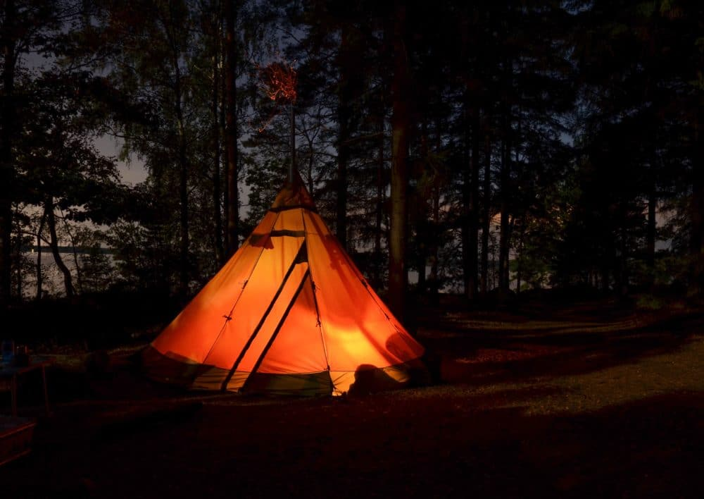 An orange canvas tent at night in the forest.