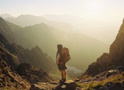 A hiker standing on a rock looking at the mountains.