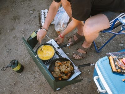 A guy cooking on a camping griddle.