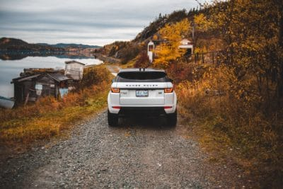 A Range Rover driving down a gravel road.
