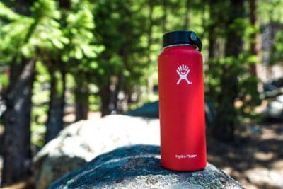 A red water bottle outdoors.